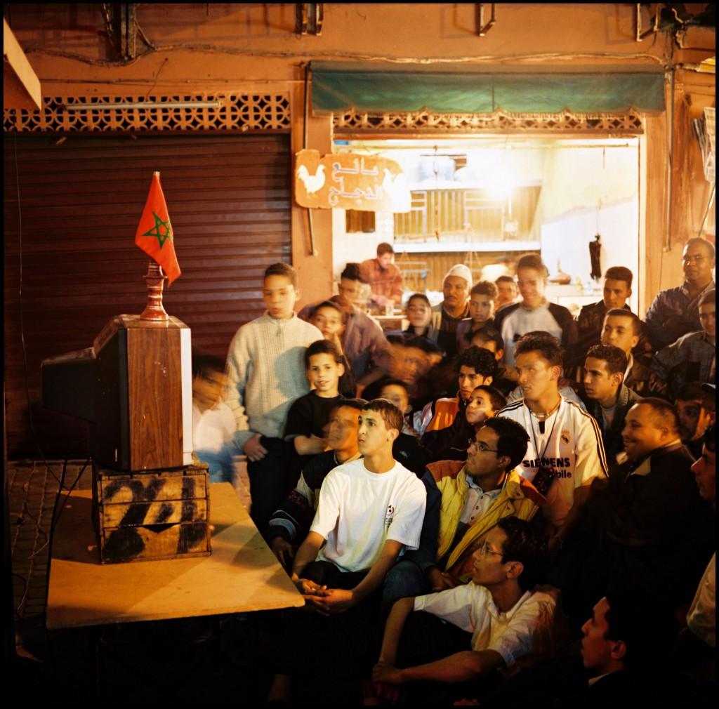 Medina, quartier de Bab Doukkala. Habitants du quartier regardant, sur une télévision installée dans la rue, la seconde demi-finale de la Coupe d'Afrique des Nations de football opposant le Maroc au Mali. Le Maroc vaincra par quatre buts à zero. Marrakech, Maroc 11/02/2004
